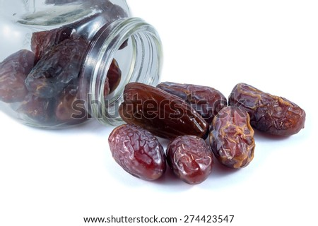 Dried dates with a glass container on white background - stock photo