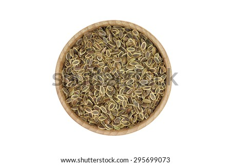 Dried fennel seeds in a wooden bowl on a white background - stock photo