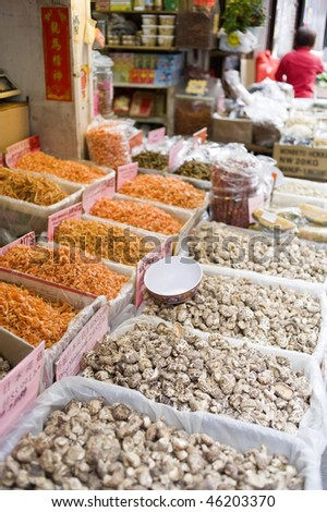 dried fish, nuts, fruit, seeds, and mushrooms displayed in bins on the sidewalk outside a store in Chinatown, New York - stock photo