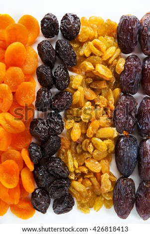 dried fruit isolated on white background. dates, raisins, dried apricots, prunes - stock photo
