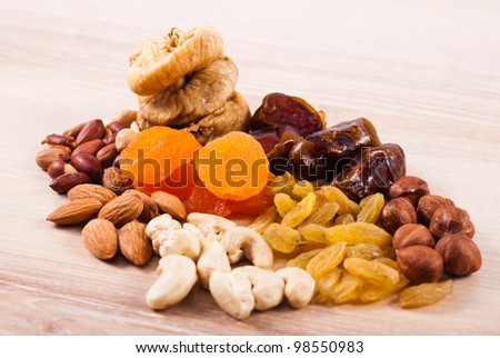 Dried fruits and nuts heaps on wooden table - stock photo