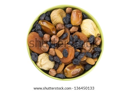 Dried fruits and nuts mixed in green bowl isolated on white - stock photo