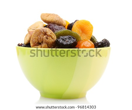 Dried fruits in green bowl isolated on white - stock photo