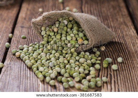 Dried green Peas (close-up shot) on wooden background - stock photo