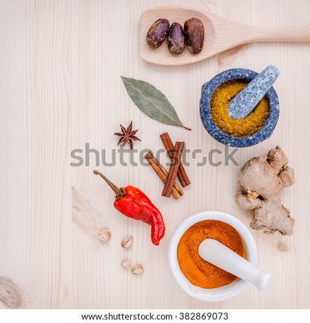 Dried herbs and spices nutmeg,star anise ,cinnamon stick ,ginger ,bay leaves and chili on wooden table. Top view with copy space. - stock photo