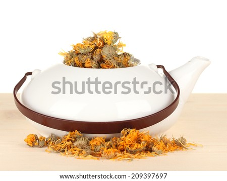 Dried herbs in teapot on wooden table, isolated on white. Conceptual photo of herbal tea. - stock photo