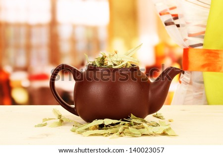 Dried herbs in teapot on wooden table, on bright background. Conceptual photo of herbal tea. - stock photo