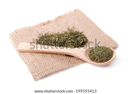 Dried herbs spices in a wooden spoon on a linen napkin - stock photo
