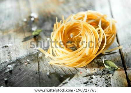 Dried Italian linguine or tagliatelli pasta in coils lying on a rustic grungy grey wooden background with copyspace - stock photo