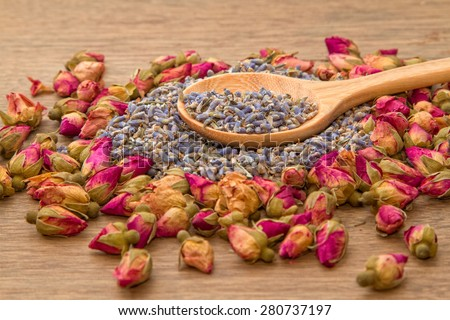 Dried lavender and rose flower tea in wooden spoon - stock photo