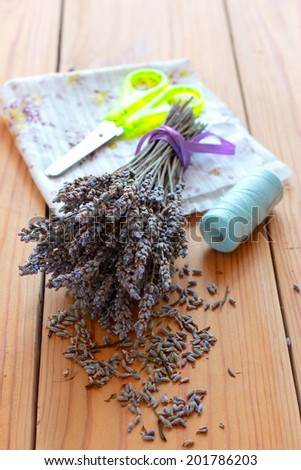 Dried lavender bouquet, scissors and cloth on the wooden table - stock photo