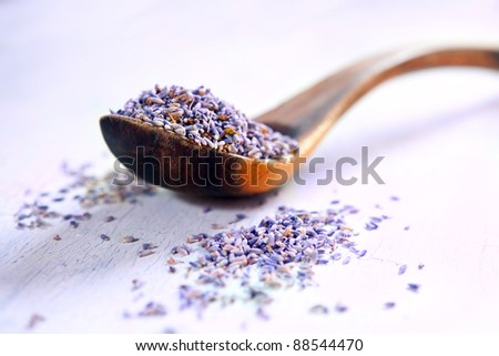 Dried lavender in a wooden spoon on a rustic table - stock photo