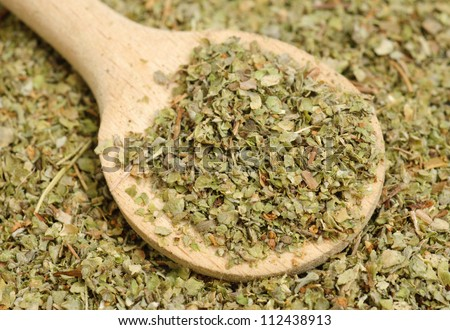 Dried marjoram spice and wood spoon as food background - stock photo