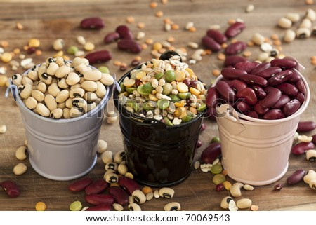 Dried mixed beans in three small containers with a shallow depth of field. - stock photo