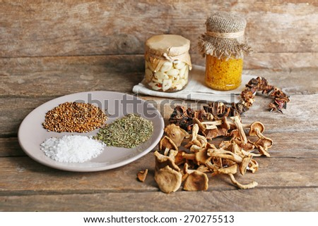 Dried mushrooms with spices on wooden background - stock photo