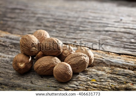 Dried nutmeg seeds set on old wooden surface - stock photo