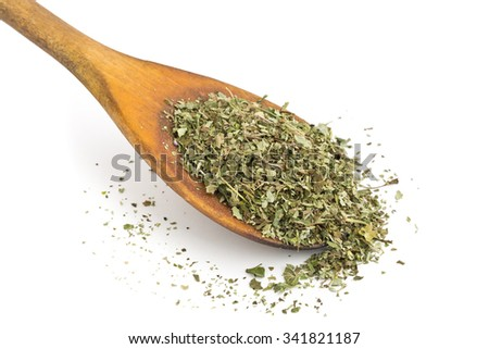Dried oregano leaves on wooden spoon over white background - stock photo