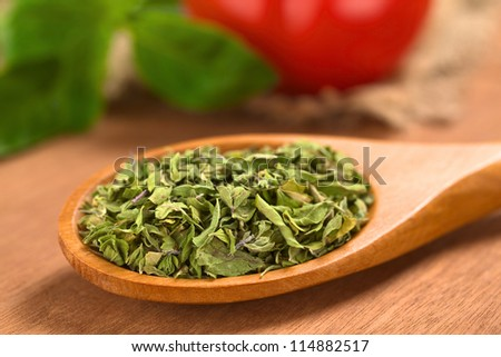 Dried oregano leaves on wooden spoon with tomato and basil in the back (Selective Focus, Focus one third into the dried oregano leaves) - stock photo