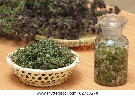 Dried oregano, wild thyme,  achillea millefolium in alcohol - stock photo