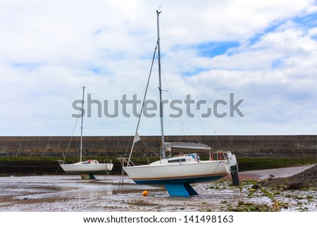 Dried out tidal harbour with sail boats resting on the keel - stock photo
