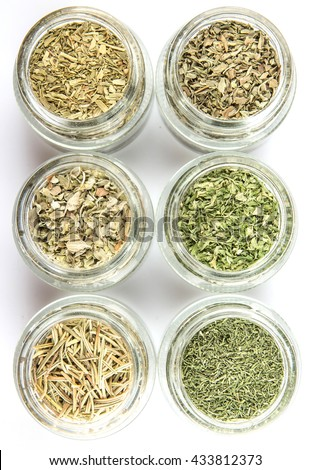 Dried parsley, estragon, marjoram, dill weed, thyme, rosemary and basil herbs in mason jar over white background - stock photo