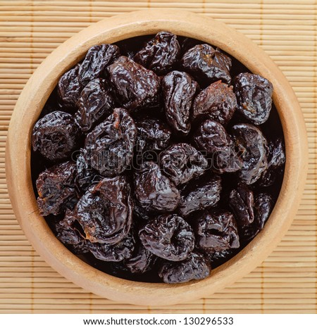 Dried prunes in wooden bowl on bamboo table cloth. - stock photo
