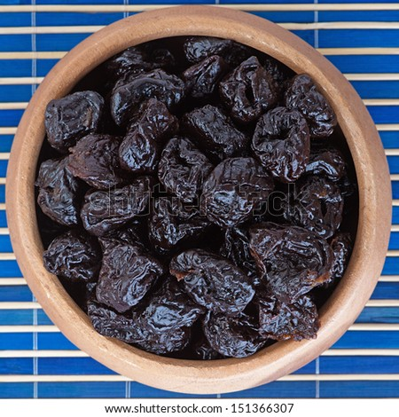 Dried prunes in wooden bowl on blue bamboo table cloth. - stock photo