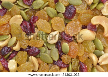 Dried raisin and cranberries, pumpkin seeds and several nuts background. - stock photo