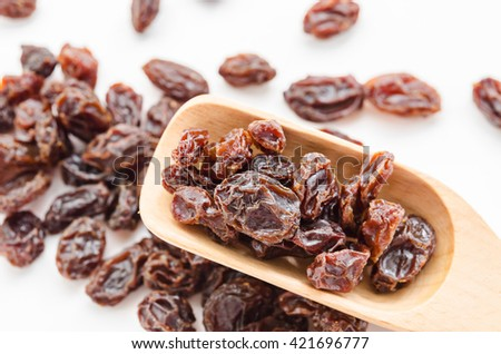 Dried raisins in wooden spoon on white background. - stock photo
