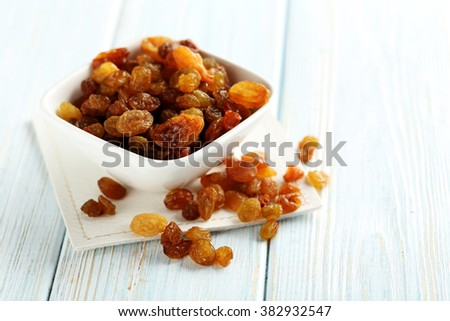 Dried raisins on a blue wooden table - stock photo