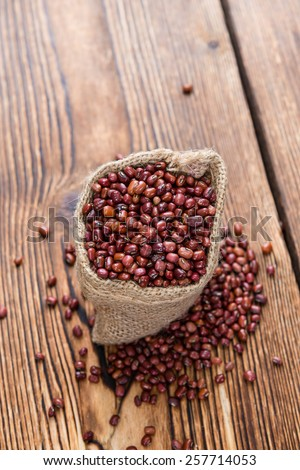 Dried red beans on dark rustic wooden background - stock photo