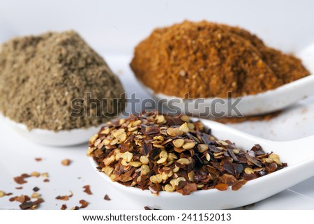 Dried red chilli flakes with other spices in white spoon - stock photo
