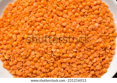 Dried red lentils. The lentil (Lens culinaris) is an edible pulse. It is a bushy annual plant of the legume family, known for its lens-shaped seeds. - stock photo