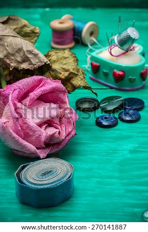 dried rose and buttons and sewing tools in refocuse.Selective focus - stock photo