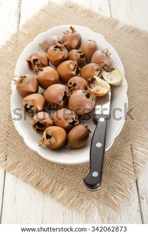 dried rose hip on a white plate with knife - stock photo