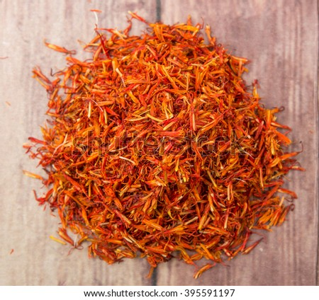 Dried safflower over wooden background - stock photo