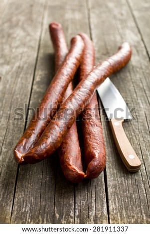 dried sausages on old wooden table - stock photo