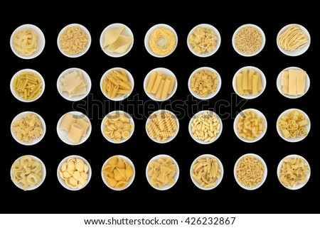 Dried spaghetti pasta food sampler in round porcelain  bowls over black background  - stock photo