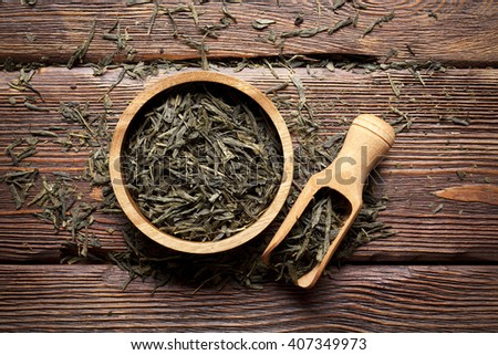 Dried tea leaves on wooden background - stock photo