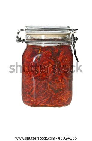 Dried tomatoes in olive oil in glass jar isolated on white. - stock photo