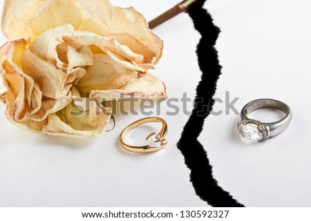 dried up rose and ripped white paper over black with rings on the paper - stock photo