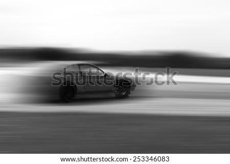 drift car motion blur on hard black and white - stock photo