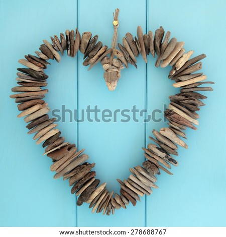 Driftwood heart hanging on a blue oak wood background. - stock photo