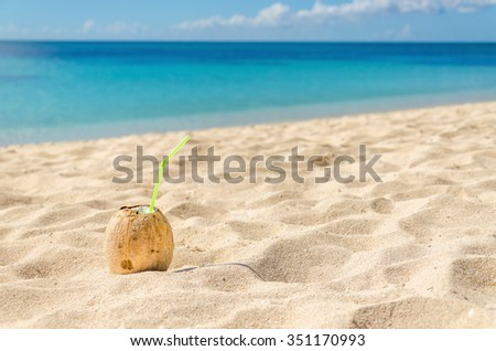 Drik with freshly broken coconut lies on a white sand Caribbean beach against the azure waters of the sea, Cuba, the Caribbean, Central America  - stock photo