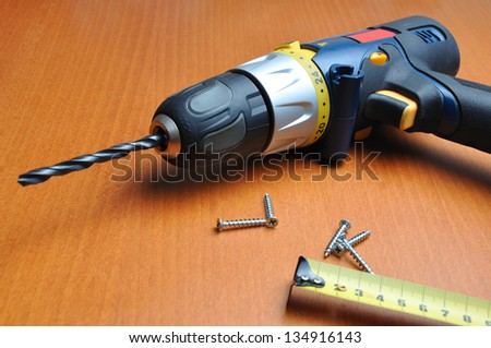 drill with roulette on wooden below - stock photo