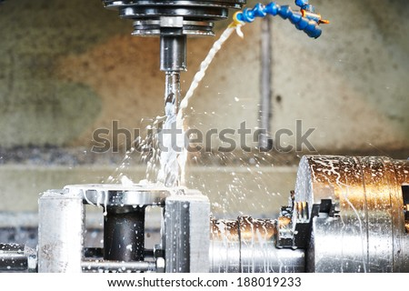 drilling hole or boring detail with lubricant liquid coolant on metal cutting machine tool at factory - stock photo