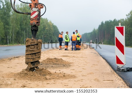 Drilling machine boring holes in ground during construction road works - stock photo