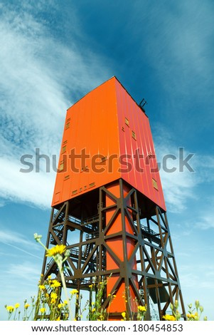 Drilling rig, mast mine and flowers - stock photo