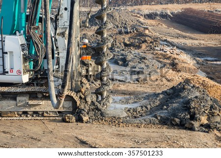 Drilling tractor installs concrete piles in the ground at construction site. Selective focus. - stock photo