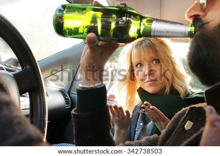 drink and drive - man drinks off a bottle of beer while driving car and passenger woman looks worried and disagree. concept of alcohol, dangerous driving - stock photo